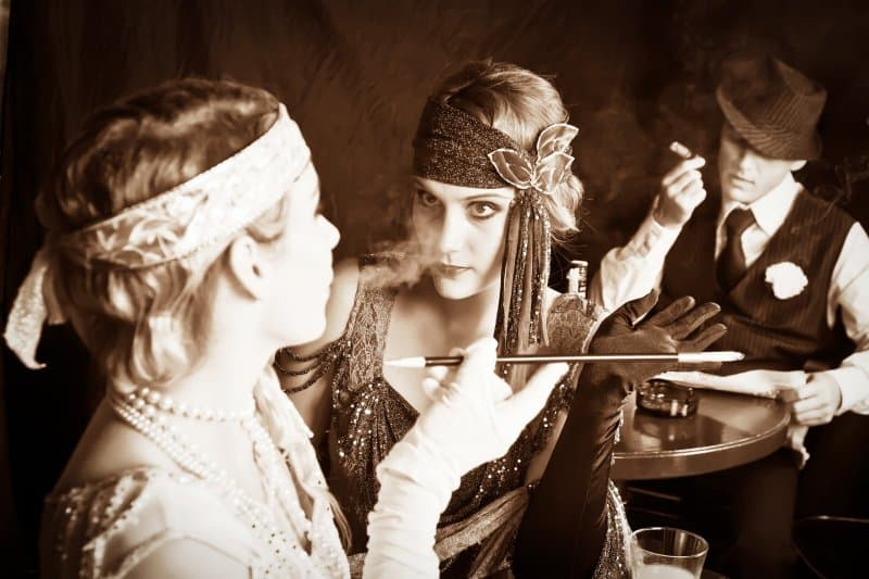 flapper girls and young gangster smoking iat the speakeasy